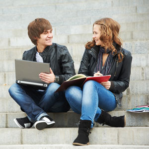 Male and female student studying on university steps